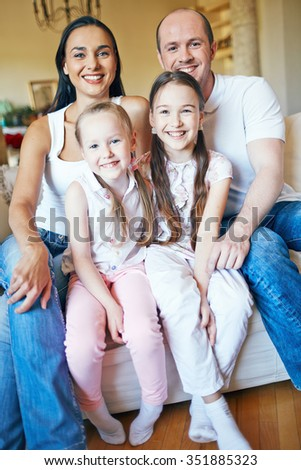 Beautiful family of four smiling at camera - stock photo