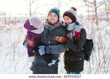 Beautiful family of three people walking in the winter forest and enjoying life - stock photo
