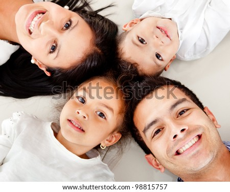 Beautiful family portrait lying on the floor with heads together - stock photo