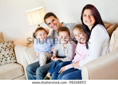 Beautiful family portrait sitting in the living room at home - stock photo