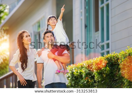 Beautiful family portrait smiling outside their new house with sunset  - stock photo