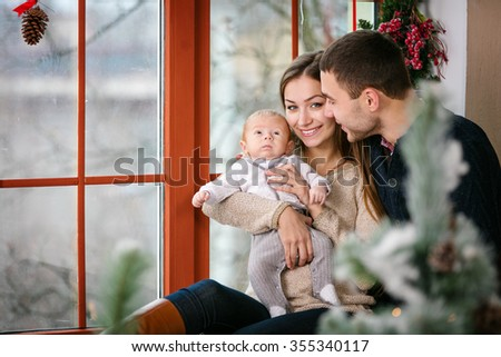 Beautiful family with a baby boy sitting near the window at home decorated for Christmas - stock photo