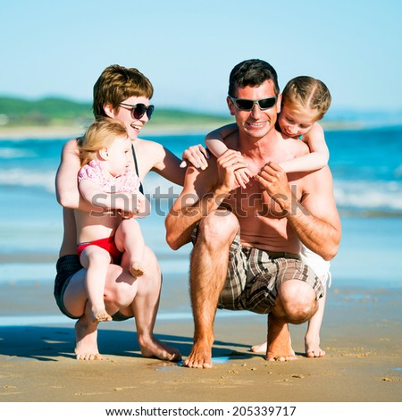 Beautiful family with two daughters having fun at the beach - stock photo