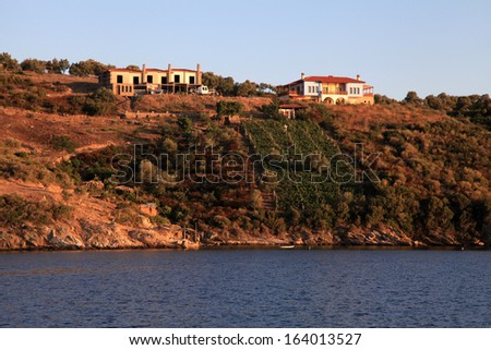 Beautiful farmland on greek island with red land, vineyard and houses above the sea, sunset lighting , Greece - stock photo