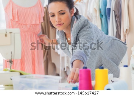 Beautiful fashion designer fixing dress on a mannequin - stock photo