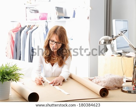 Beautiful fashion designer sitting at desk and working in her studio.  - stock photo