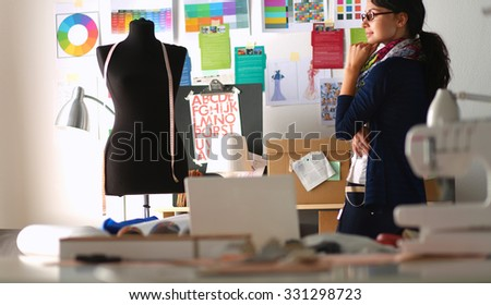 Beautiful fashion designer standing in studio - stock photo