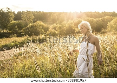 beautiful fashion girl in white dress stand against wild grass, forest and bush in sunny rays field at sunset in summer meadow. Alone Cute young adult blond woman enjoy warm evening White dress - stock photo