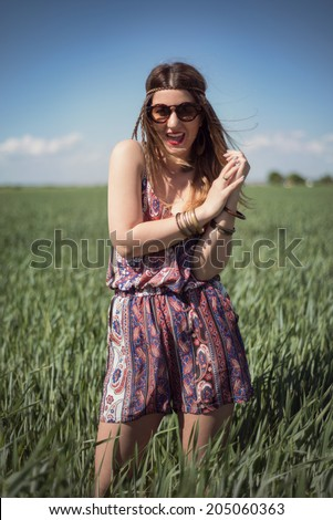 Beautiful fashion hippie woman in a wheat field wearing a boho jumpsuit romper and sunglasses, with the wind blowing in her blonde hair - stock photo