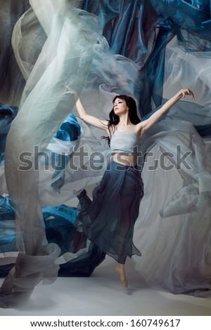 Beautiful fashion model dancing with blue fabrics. - stock photo