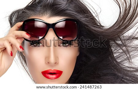 Beautiful fashion model girl with healthy long hair in motion holding her shades on forehead while looking at camera. Isolated on white background. Beauty and fashion concept. - stock photo