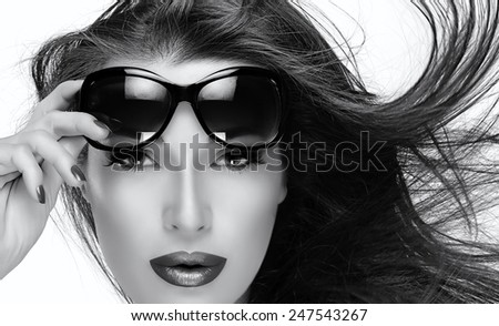 Beautiful fashion model girl with healthy long hair in motion holding her shades on forehead while looking at camera. Monochrome portrait Isolated on white. Beauty and fashion concept. - stock photo