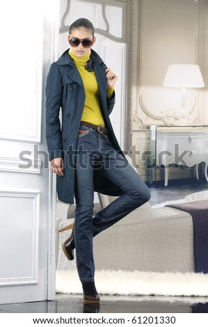 Beautiful fashion model in blue jeans wearing sunglasses posing in the studio - stock photo