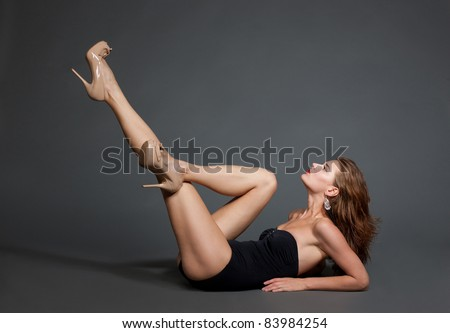 Beautiful fashion model in swimsuit on dark grey background - stock photo
