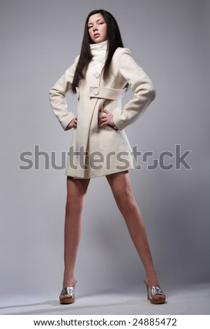 Beautiful fashion model posing in white coat. - stock photo