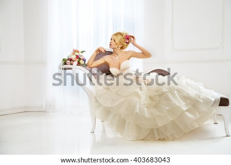 Beautiful fashion model. Sensual bride. Woman with wedding dress, hair and make up. Waiting for groom on background of window. Natural manicure. Beauty spring girl with bouquet of flowers in hands - stock photo
