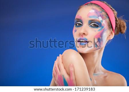 beautiful fashion woman color face art portrait on blue background - stock photo