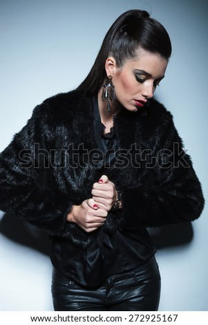 Beautiful fashion woman looking down while pulling her fur coat. - stock photo