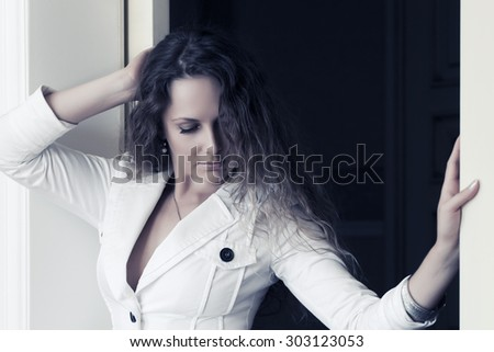 Beautiful fashion woman with long curly hairs at apartment - stock photo
