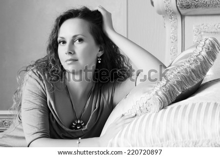 Beautiful fashion woman with long curly hairs in a bedroom  - stock photo