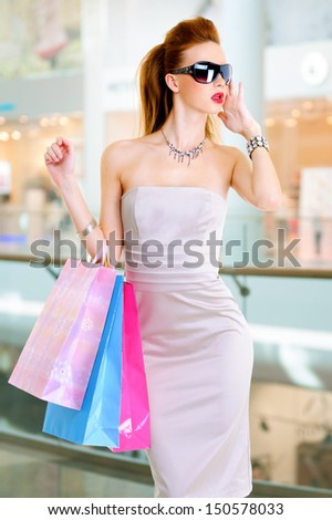 Beautiful fashion woman with shopping bags stands at shop - stock photo