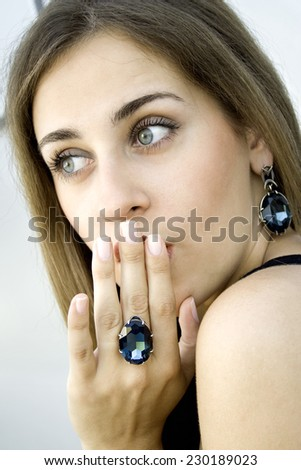 Beautiful fashionable girl on the ring finger is clothed with a large blue gemstone - stock photo