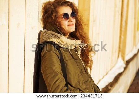 Beautiful fashionable girl posing with glasses on a sunny day near the wall - stock photo