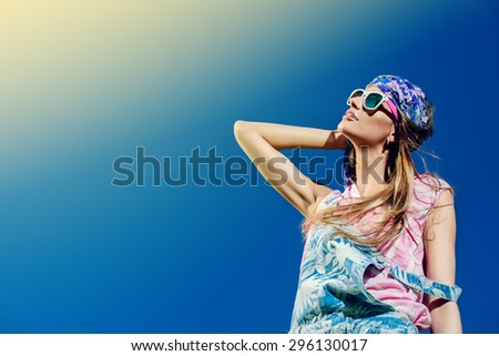 Beautiful fashionable girl wearing jeans clothes posing over blue sky. Summer style. Holidays. - stock photo
