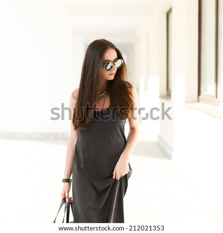 Beautiful fashionable girl with glasses and a dress is on a sunny day - stock photo
