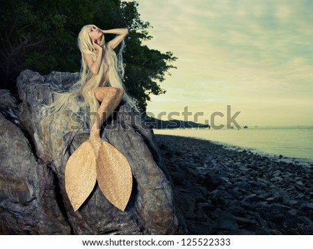 Beautiful fashionable mermaid sitting on a rock by the sea - stock photo