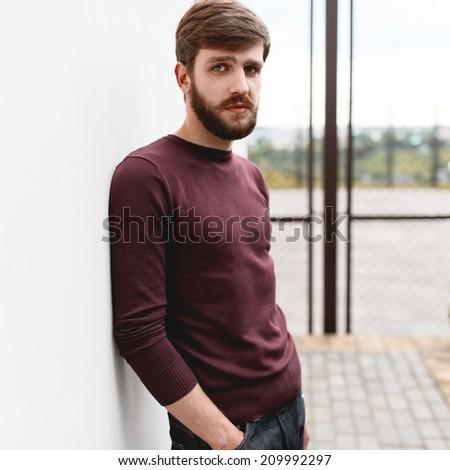 Beautiful fashionable stylish man with a beard standing near the wall - stock photo