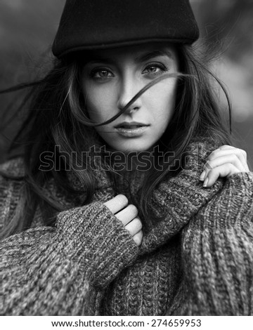 Beautiful fashionable woman in a hat standing in the wind - stock photo