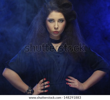 Beautiful fashionable woman in black dress. Studio shot in smoke.  - stock photo