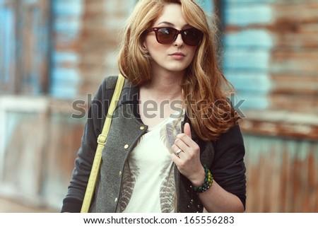 Beautiful fashionable woman in sunglasses walking in the street - stock photo