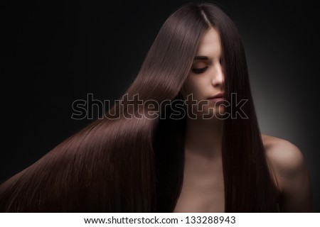 beautiful fashionable woman with long hair on dark background - stock photo