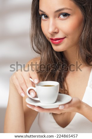 Beautiful fashionable young brunette with a cup of coffee. - stock photo