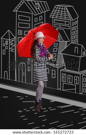 Beautiful fashionable young girl with red umbrella in the street - stock photo