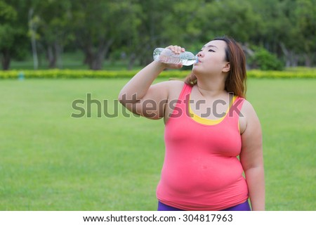 Beautiful fat woman drinking water after finish her workout. - stock photo