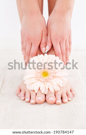 Beautiful feet. Close-up of young woman touching her feet while standing on hardwood floor - stock photo