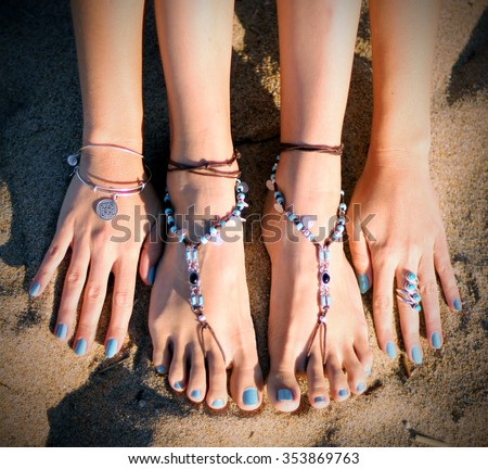 Beautiful feet jewelry on the beach - stock photo