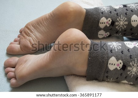 Beautiful feet of a woman are waiting for massage on a white towel on blue background. Woman wears grey winter leggings with snowflakes and snowman on it. - stock photo