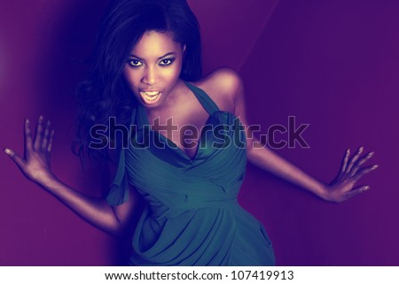 Beautiful feisty vivacious African dancer in a green dress with large curvy breasts enjoying herself - stock photo