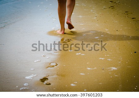 Beautiful female a foot in the beach - stock photo