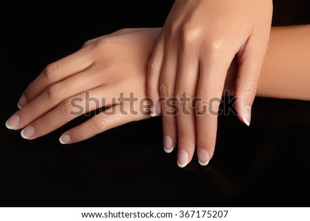 Beautiful female arms with ideal french manicure on black background. Care about female hands, healthy soft skin. Spa & cosmetics. Beauty care. Close-up of beautiful famele fingers with nails polish  - stock photo
