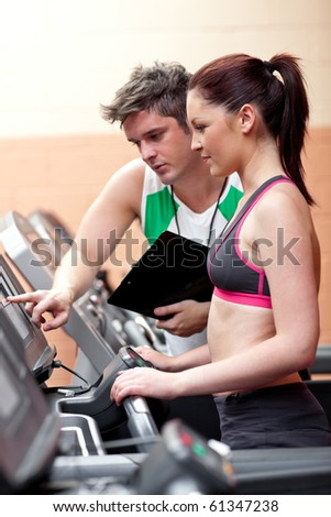 Beautiful female athlete standing on a running machine talking with her personal coach in a fitness center - stock photo