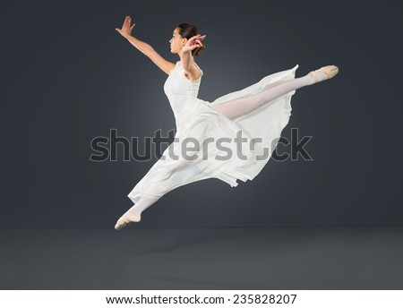 Beautiful female ballet dancer on a grey background. Ballerina is wearing a  tutu and point shoes. - stock photo