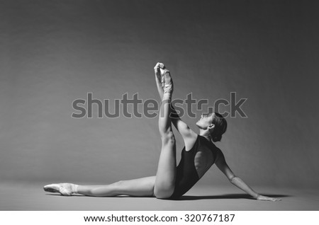 Beautiful female ballet dancer posing. Studio shot, grayscale image. - stock photo