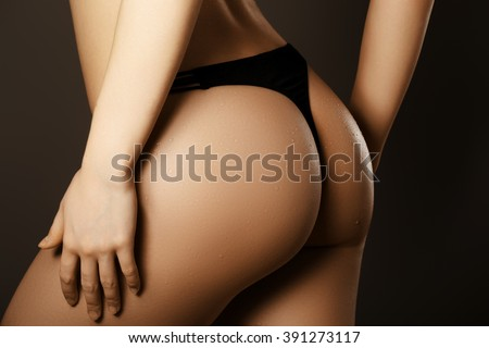 Beautiful female body part. Sexy female buttocks isolated on black background. Beautiful female slim body.Beauty part of female body. Woman's shape with clean skin. Healthy lifestyle, itness   - stock photo