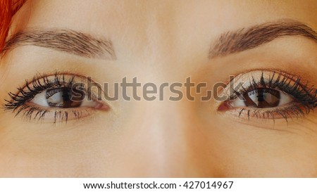 Beautiful female brown eyes with long eyelashes. Close up of brown woman eyes looking at camera, smiling, squinting and blinking. Emotions. Beautiful girl eyes and eyelashes. Attractive female face. - stock photo