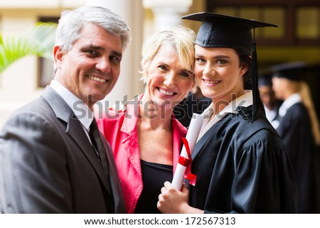 beautiful female college graduate with parents on graduation day - stock photo